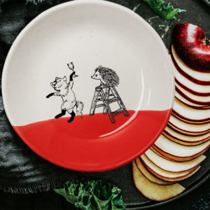 This plate is handmade by the hedgehogs of Darn Pottery and has a drawing of a fox celebrating with a champagne and a hedgehog climbing a ladder. Red accent color.