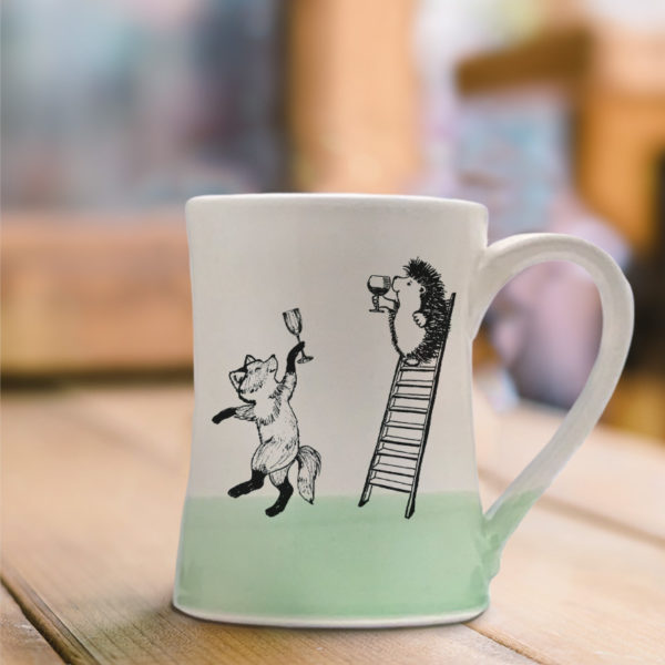 celebration mug with fox and hedgehog toasting each other