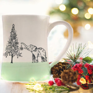 Handmade coffee mug with a drawing of either a very short elephant or a really tall christmas tree. Green accent color.
