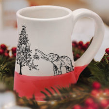 Handmade coffee mug with a drawing of either a very short elephant or a really tall christmas tree. Red accent color.