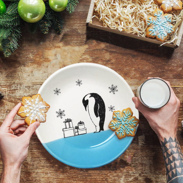 Handmade ceramic plate with a drawing of an Emperor Penguin examining his stack of presents in the snow. Blue accent color.