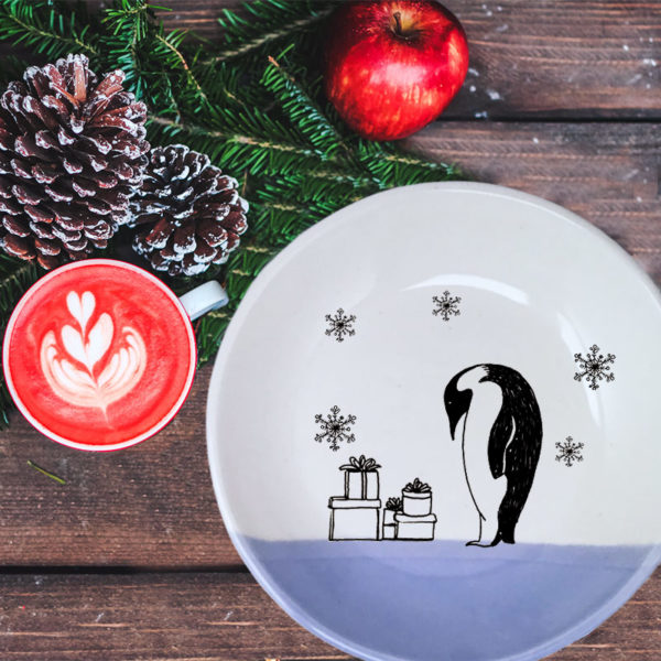 Handmade ceramic plate with a drawing of an Emperor Penguin examining his stack of presents in the snow. Lavender accent color.