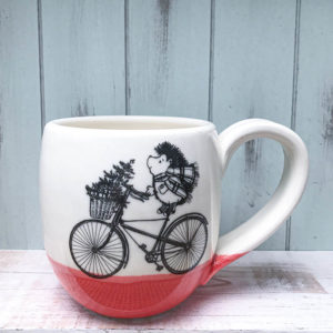 Cocoa mug with hedgehog on bike delivering christmas tree