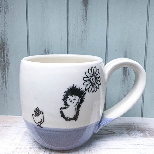 cocoa mug with hedgehog flying in on a flower