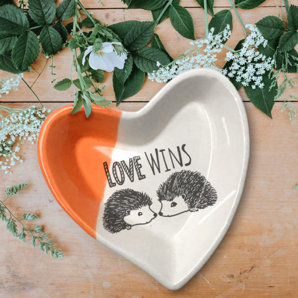 Handmade ceramic heart-shaped dish with drawing of two hedgehogs and the words Love Wins. Coral accent color