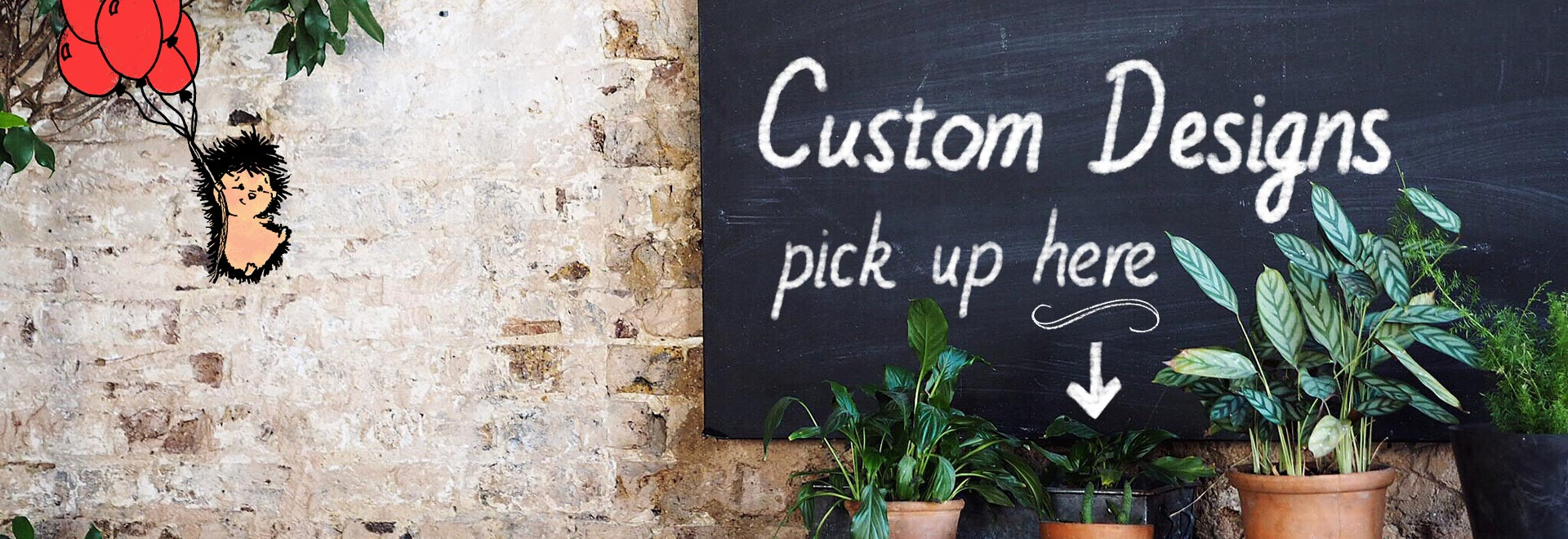 "A chalkboard on a brick wall with text ""Custom Designs"""