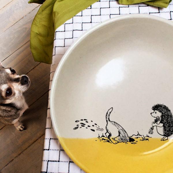This ceramic plate is handmade by hedgehogs at Darn Pottery and has a drawing oof a dog digging in the yard while hedgehog looks on. Gold accent color