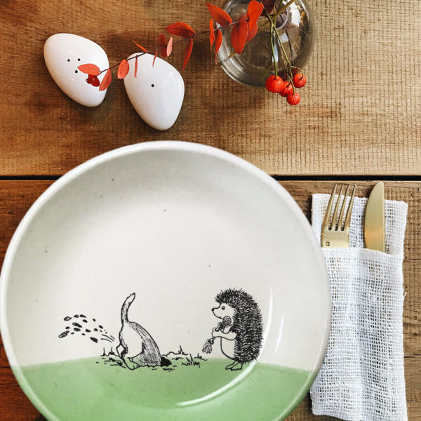 This ceramic plate is handmade by hedgehogs at Darn Pottery and has a drawing oof a dog digging in the yard while hedgehog looks on. Green accent color