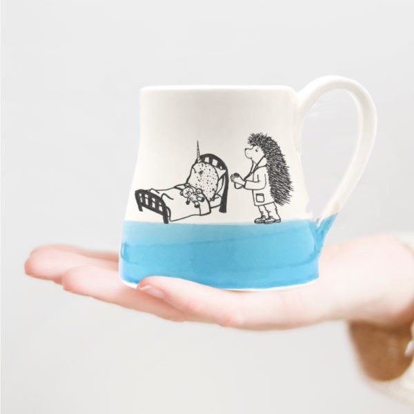 Handmade wheelthrown mug with drawing of a doctor hedgehog taking care of an ill narwhal