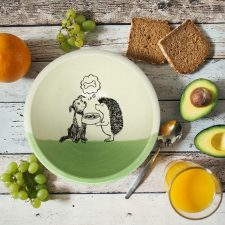 This handmade ceramic soup bowl has a cute drawing of a hedgehog offering a bowl of kibble to a dog. The dog, meanwhile, is dreaming of a bone. Green accent color