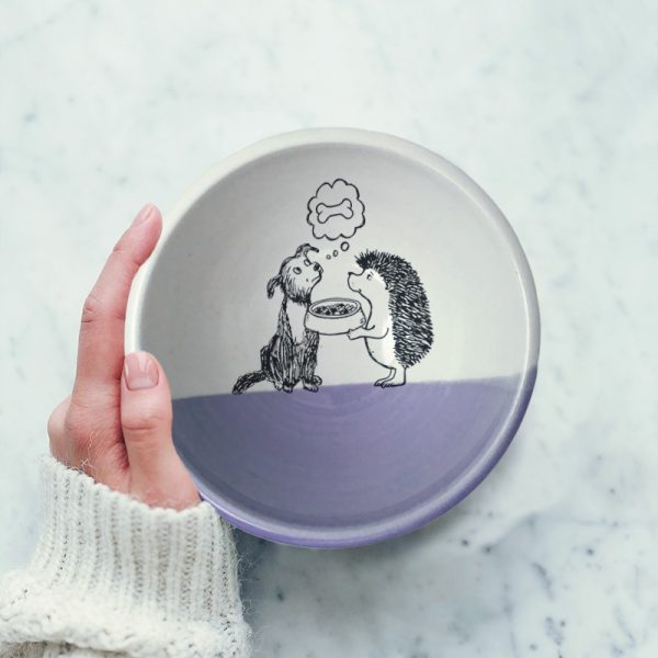 This handmade ceramic soup bowl has a cute drawing of a hedgehog offering a bowl of kibble to a dog. The dog, meanwhile, is dreaming of a bone. Lavender accent color