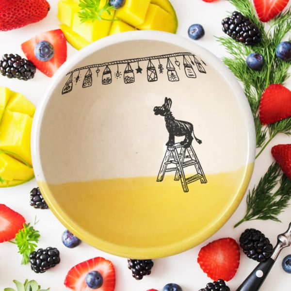 This soup or cereal bowl is handmade and features a drawing of a tiny donkey, standing on a step-ladder, looking at a string of lights overhead. Gold accent color.