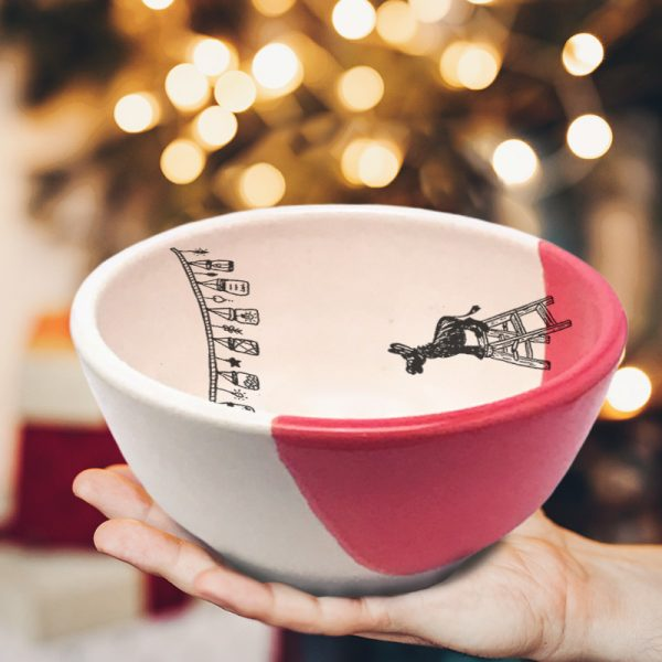 This soup or cereal bowl is handmade and features a drawing of a tiny donkey, standing on a step-ladder, looking at a string of lights overhead. Red accent color.