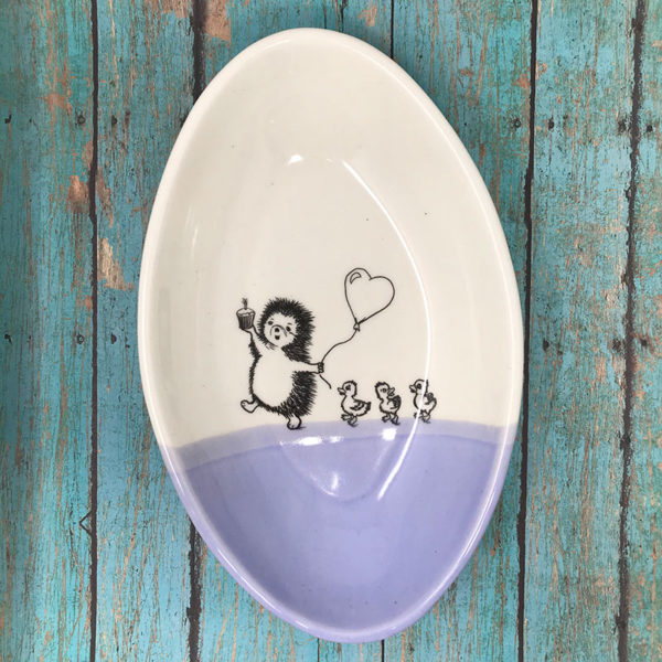 Handmade dish with drawing of a hedgehog leading ducklings to a party