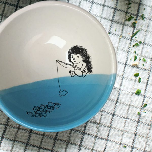 This soup bowl is for the fisherman or woman in your life. It holds fish stew, cereal or minestrone with equal panache and features a drawing of a hedgehog fishing. Blue accent color.