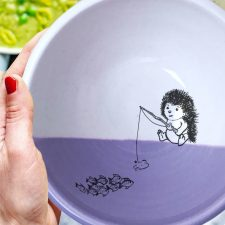 This soup bowl is for the fisherman or woman in your life. It holds fish stew, cereal or minestrone with equal panache and features a drawing of a hedgehog fishing. Lavender accent color.