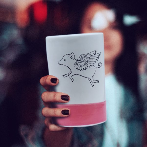 A lovely ceramic tumbler handmade by hedgehogs and illustrated with a really cute flying pig. Red accent color.