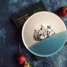 Unlikely best friends, chicken and fox are the featured drawing on this perfect soup bowl that was handmade and illustrated by the hedgehogs of Darn Pottery. Blue accent color.