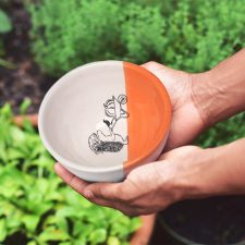 A happy little hedgehog is rolling a wheelbarrow with a giant pumpkin. This cute illustration is featured on a lovely handmade ceramic soup or salad bowl from Darn Pottery. Coral accent color
