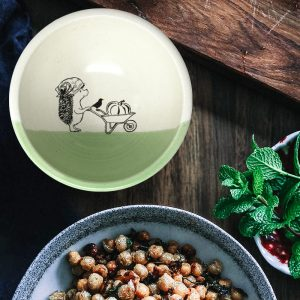 A happy little hedgehog is rolling a wheelbarrow with a giant pumpkin. This cute illustration is featured on a lovely handmade ceramic soup or salad bowl from Darn Pottery. Green accent color