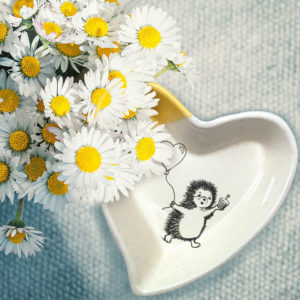 Handmade ceramic heart shaped dish with a drawing of hedgehog heading to a party with a cupcake and a balloon. Gold accent color