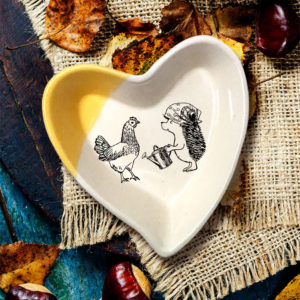Handmade ceramic heart-shaped dish with drawing of a famer hedgehog talking to her chicken. Gold accent color