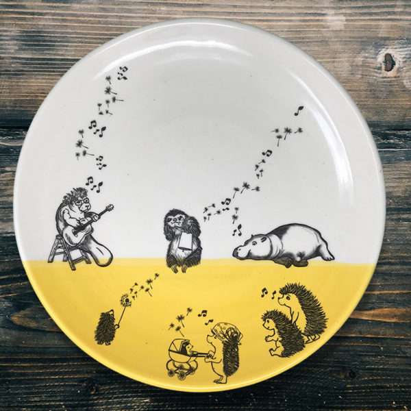 dinner plate with drawing of a manatee, a sloth, a hippo and a family of hedgehogs singing together