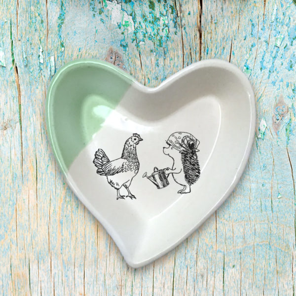 Handmade ceramic heart-shaped dish with drawing of a famer hedgehog talking to her chicken. Green accent color