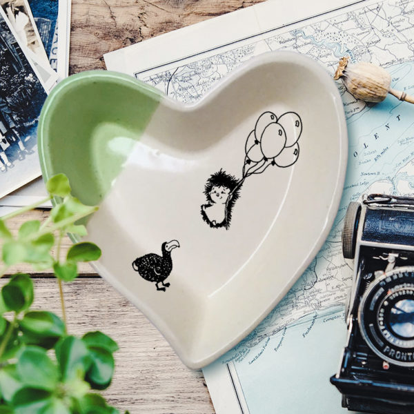 Handmade ceramic heart-shaped dish with drawing of hedgehog and dodo. Green accent color