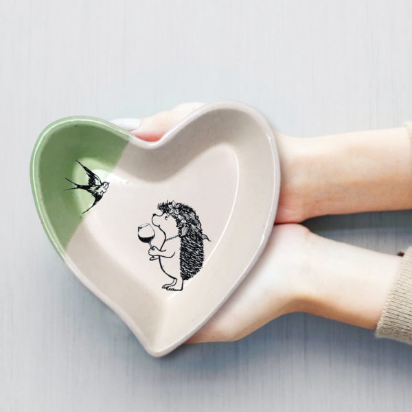 Handmade ceramic heart-shaped dish with drawing of a girl hedgehog with wine. Green accent color