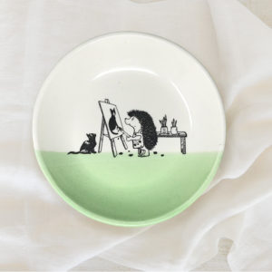 green salad plate with drawing of an artist hedgehog painting a cat