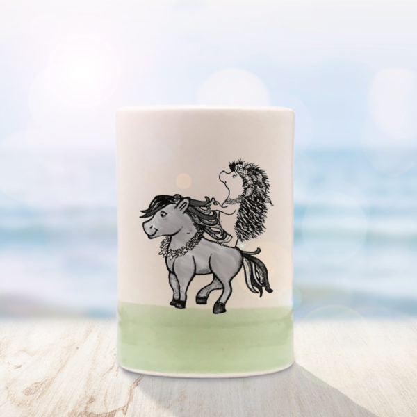 Green Darn Pottery tumbler with drawing of a Hawaiian hedgehog riding a horse wearing a lei