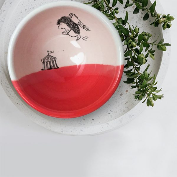 A hedgehog with a jetpack is flying away from the circus.This is happening inside this lovely ceramic soup bowl made by hand in Tennessee. Red accent color