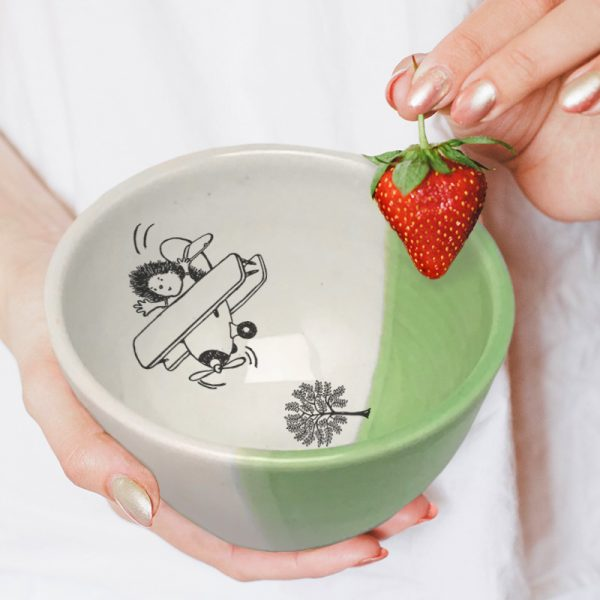 A hedgehog flying a biplane over the treetops. This is the original illustration on this handmade certamic soup bowl. Green accent color