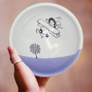 A hedgehog flying a biplane over the treetops. This is the original illustration on this handmade certamic soup bowl. Lavender accent color