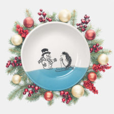Handmade salad plate with a drawing of a hedgehog on skis greeting a well-dressed snowman. Blue accent color