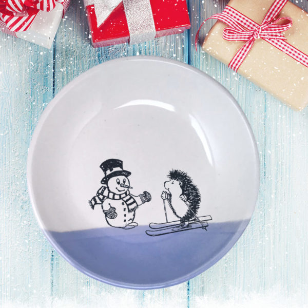 Handmade salad plate with a drawing of a hedgehog on skis greeting a well-dressed snowman. Lavender accent color