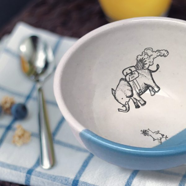 A perfectly sized handmade ceramic bowl for soup with a drawing of an elephant flying over a startled chicken. Blue accent color