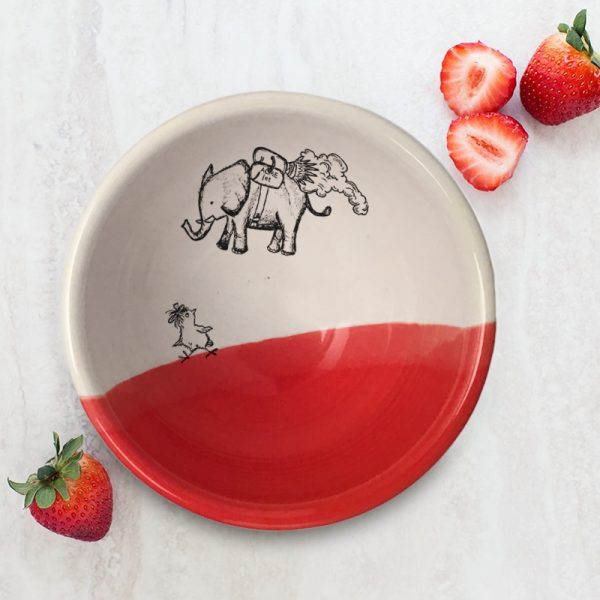 A perfectly sized handmade ceramic bowl for soup with a drawing of an elephant flying over a startled chicken. Red accent color