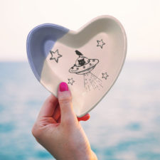 Handmade ceramic heart shaped dish with a drawing of a cat in a flying saucer or UFO. Lavender accent color.