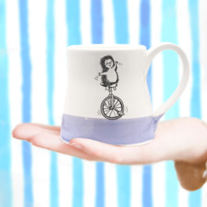small mug with drawing of a hedgehog on a unicycle