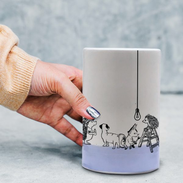 This handmade ceramic tumbler tells the epic tale of an attempt by a rag-tag group of woodland animals to replace a tired, though not quite dead, lightbulb. Lavender accent color.