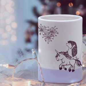 A handmade ceramic tumbler with a drawing of the cutest damned hedgehog doing pirouettes on a unicorn. Rediculous. Lavender accent color.