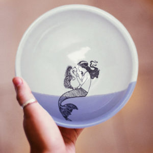 Handmade soup bowl with drawing of a mermaid kissing a hedgehog. Lavender accent color