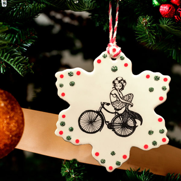 Handmade ceramic ornament with drawing of a mermaid riding a bicycle. Reverse side text reads Nevertheless, she persisted.