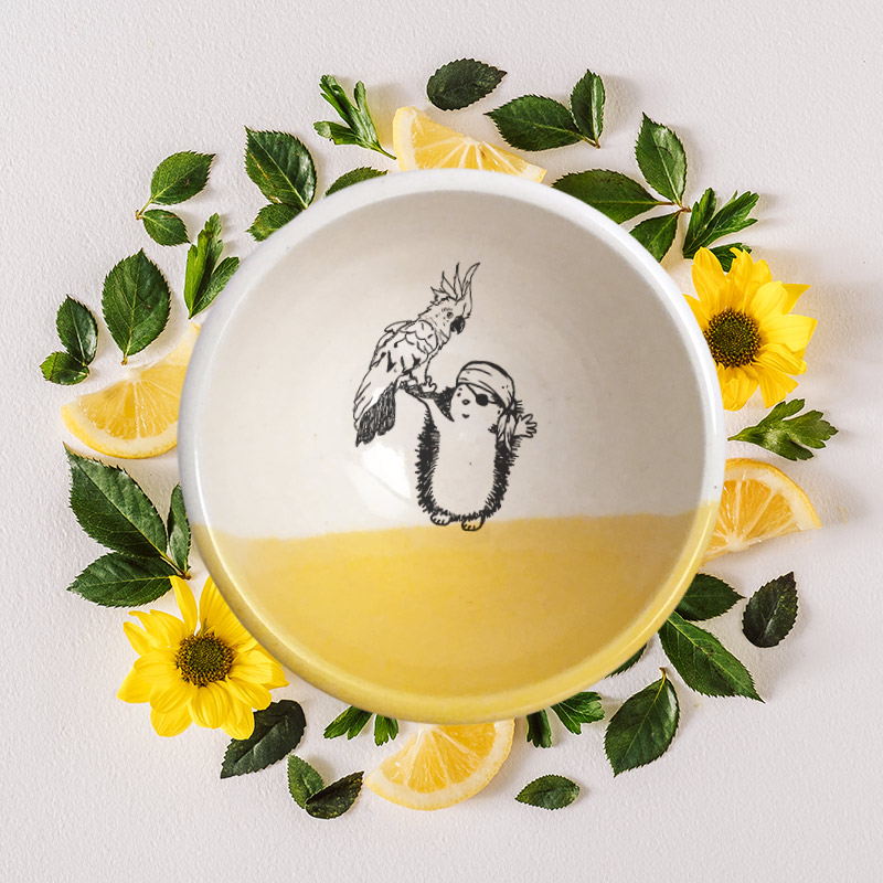 No pirate is complete without a sidekick. The parrot and the hedgehog pirate are a great team and are featured in the drawing on this handmade ceramic bowl. Gold accent color.