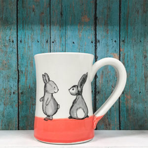 Handmade ceramic mug with drawing of two cute rabbits. Red accent color