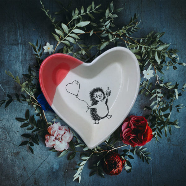 Handmade ceramic heart shaped dish with a drawing of hedgehog heading to a party with a cupcake and a balloon. Red accent color