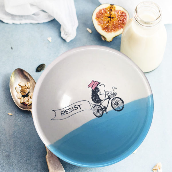 This handmade ceramic soup bowl has a drawing of a brave hedgehog resistance fighter, riding a bike with a huge resist banner. Blue accent color.