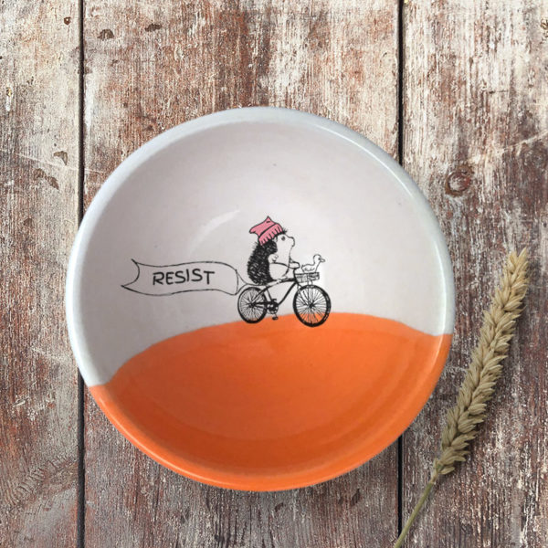 This handmade ceramic soup bowl has a drawing of a brave hedgehog resistance fighter, riding a bike with a huge resist banner. Coral accent color.